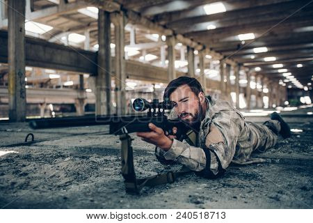 Attractive And Serious Guy Is Lying On The Ground In A Big Hangar. He Is Taking Aim. Man In Looking