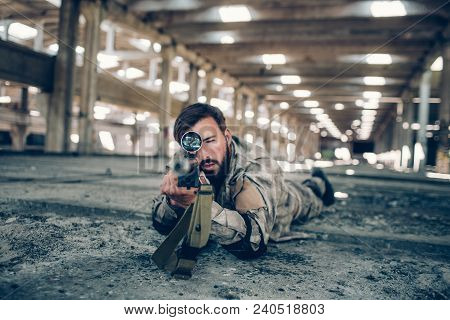 A Picture Of Fighter Lying On The Floor In Big Hangar. He Is Looking Straight Forward Through Lens A