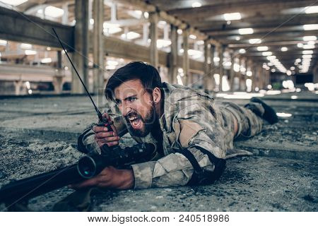 Warrior Is Screaming In Portable Radio. He Is Lying On The Ground With Big Rifle. Guy Has Protection