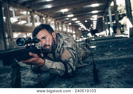 Calm And Peaceful Young Man Is Lying On The Ground And Taking Aim. He Looks Very Serious. Guy Is Usi
