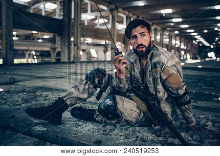 Nice Picture Of Attractive And Handsome Brunette Sitting On The Ground. He Is Holding Portable Radio