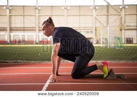 A Shot of young athlete at starting position ready to start a race.Sprinter ready for race poster