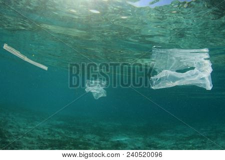 Plastic ocean pollution. Plastic bags, bottles and straws pollute sea