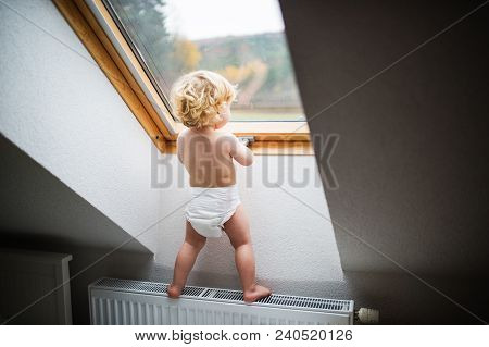 Little Toddler Boy Standing On A Radiator, Opening A Window. Domestic Accident. Dangerous Situation