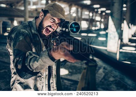 Fighter Is Looking Through Lens On Rifle And Taking Aim. He Is Holding It With Both Hands. Emotional