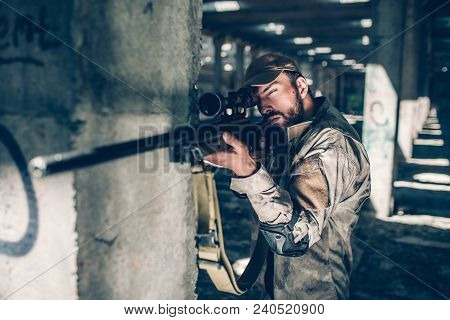 Calm And Quiet Adult Is Looking Through Lens. He Is Taking Aim. Guy Is Standing Besides Column And W