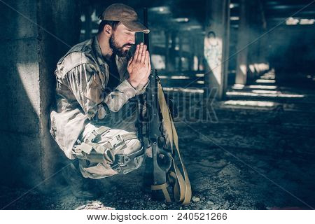 Spiritual Man Is Sitting In Squat Position And Praying. He Is Keeping His Eyes Closed And Holding Ha