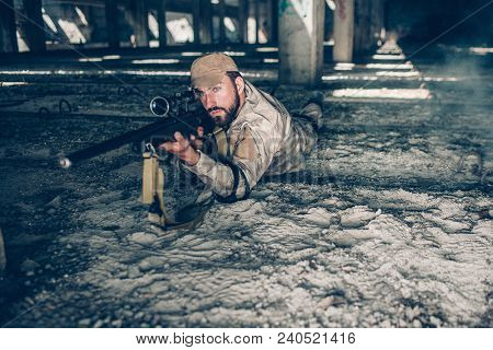 Serious And Professional Man Is Lying On The Ground And Looking Through Lens. He Is Taking Aim. Guy
