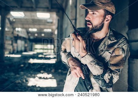 Horizontal Picture Of Soldier Talking To Portable Radio. He Is Holding It In Left Hand. There Ir A G
