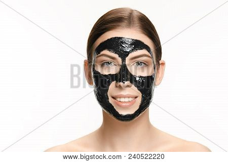 Young beautiful caucasian woman applying a black cosmetic mask for the face of the therapeutic black mud. Spa treatment and face beauty concept. Female face care and perfect skin concepts poster