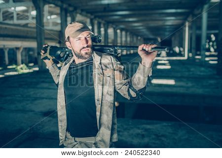 Calm And Peaceful Commandor Is Standing And Posing. He Is Looking Aside. Also Guy Has A Rifle In His
