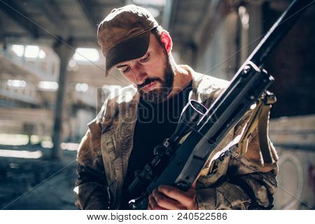 A Picture Of Warrior Standing In A Hangar And Looking Down At His Rifle. He Is Cleaning It And Prepa