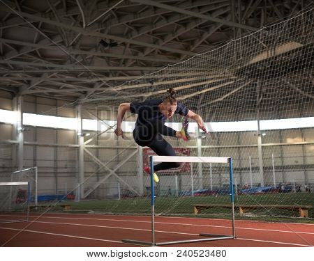 The shot of concentrated male track and field athlete jumping over the hurdle.Indoor training poster