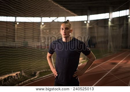 The Portrait Of Concentrated Track And Field Athlete Preparing For The Start.looking At Camera