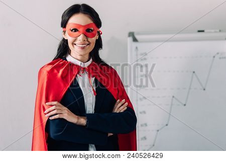 Portrait Of Smiling Attractive Super Businesswoman In Cape And Mask Looking At Camera In Office