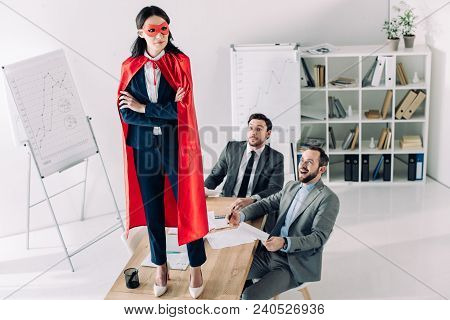 Super Businesswoman In Mask And Cape Standing On Table In Office