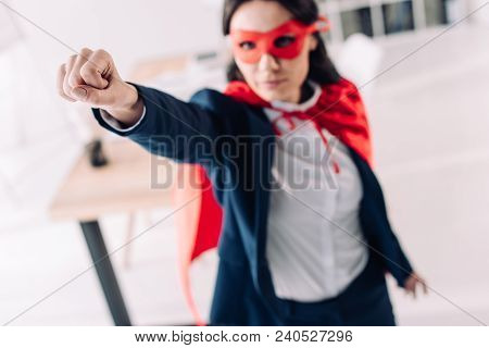 Attractive Super Businesswoman In Cape And Mask Standing With Hand Up In Office
