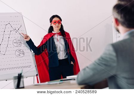 Super Businesswoman In Mask And Cape Showing Presentation For Businessman In Office