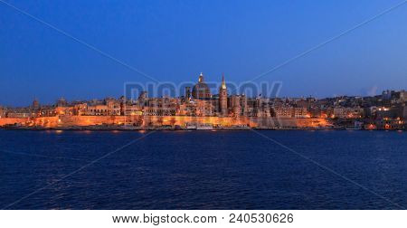 Valletta, Malta in the evening. Panoramic view of illuminated historic island under a clear blue sky, the dome of Carmelite Church and St Paul`s tower.