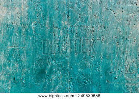 Weathered blue, green painted wall background, partially faded. Corroded, peeled, vintage, blank wall for backdrop. Close up view with details.