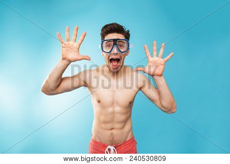 Portrait of a cheerful young shirtless man in swim mask looking at camera over blue background