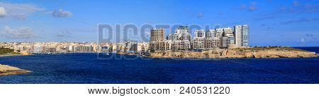 Malta, Valletta. Sliema town with multistorey waterfront buildings, blue sea and blue sky with few clouds background. Panoramic view, banner.