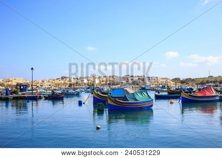 Marsaxlokk historic harbour full of wooden boats in Malta. Blue sky and village background. Destination for vacation, relaxing and fishing.