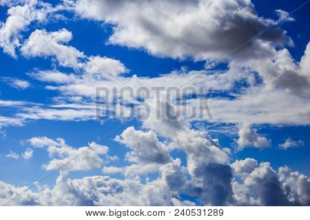 White clouds hanging from blue sky for backdrop. Scattered clouds on daylight, skyline from under view.