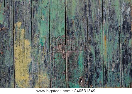 Wooden door background, colorful and peeled. Timeworn entrance provides safety and privacy. Close up view with details.