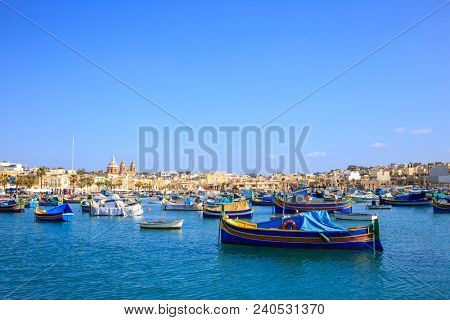 Malta, Marsaxlokk historic harbor full of boats. Destination for vacation, relaxing and fishing. Blue sky and village background.