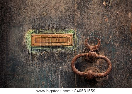Wooden brown door background with rusty letterbox and doorknob. Timeworn closed entrance, close up view with details.