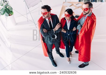 High Angle View Of Super Businesspeople In Masks And Capes With Crossed Arms In Office