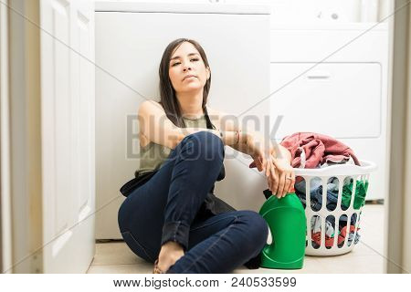 Beautiful Housewife Feeling Restless Sitting In Laundry Room With Back Support Of Washing Machine Wi