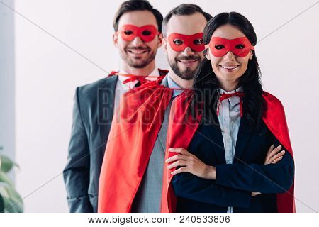Super Businesspeople In Masks And Capes Looking At Camera In Office