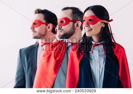 Super Businesspeople In Masks And Capes Looking Away In Line In Office