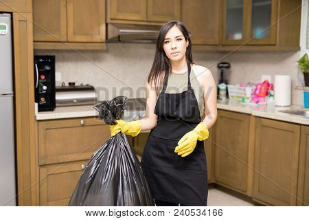 Housewife Wearing Black  Apron And Yellow Protective Rubber Gloves Holding Garbage Bag