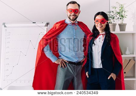 Smiling Super Businessman And Super Businesswoman Looking At Camera In Office
