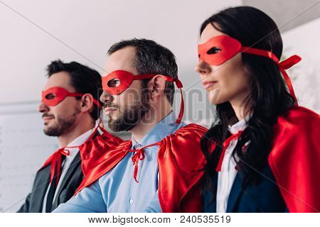 Side View Of Super Businesspeople In Masks And Capes Looking Away In Office