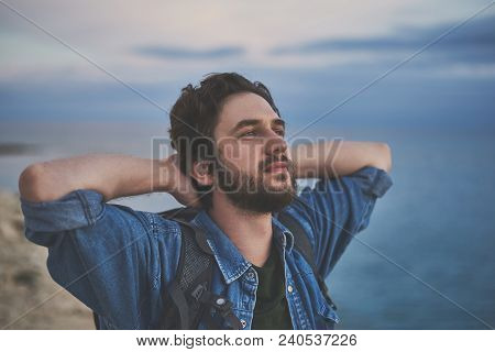 Peaceful Male Traveler Is Breathing Fresh Air At The Seaside With Enjoyment. He Is Raising Arms Behi