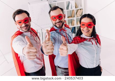 Super Businesspeople In Masks And Capes Showing Thumbs Up In Office