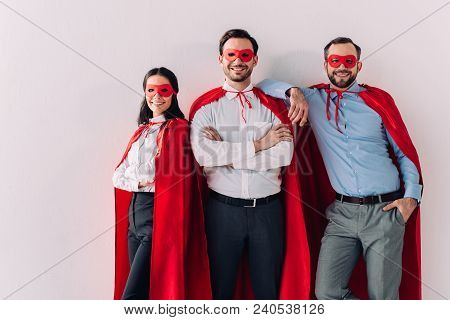 Smiling Super Businesspeople In Masks And Capes Looking At Camera Isolated On White