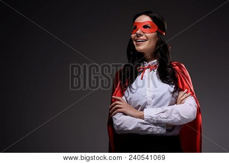 Smiling Attractive Super Businesswoman In Red Cape And Mask Standing With Crossed Arms Isolated On B