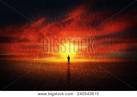Futuristic Scenery View As A Man Silhouette Walking On A Dry Desert Ground Over Sunset Background An