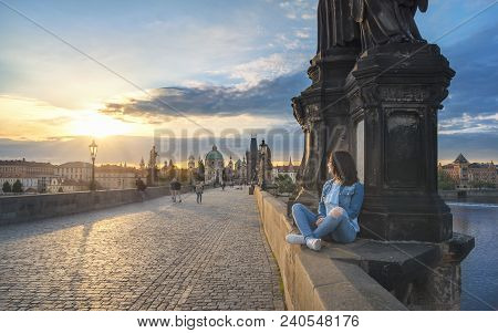 Young Brunette Woman, Sitting Relaxed On The Charles Bridge Walls, Over The Vltava River, Admiring T