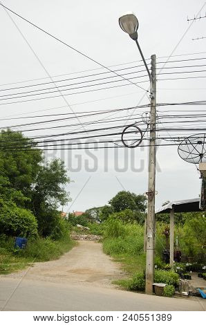 Street Lamp And Many Wires Messy With Power Line Cables At Beside Road In Uthai Thani, Thailand