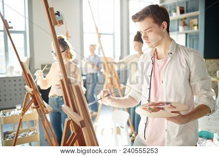 Serious guy concentrating on his painting on easel during lesson in school of arts