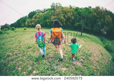 A Woman With Children Goes Hiking. The Woman Took Her Sons By The Arms. Traveling With Family. The B