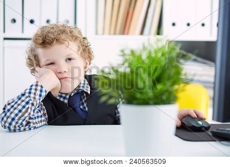 Cute Little Boy Holds His Head On His Hand, Imitating Tired Office Worker Or Businessperson.portrait