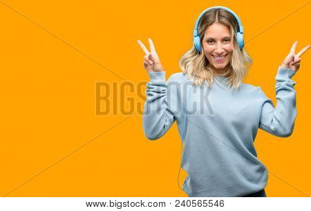 Young beautiful woman listening to music looking at camera showing tong and making victory sign with fingers