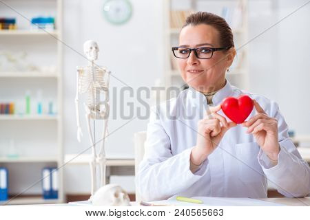 Cardiologist with red heart in medical concept